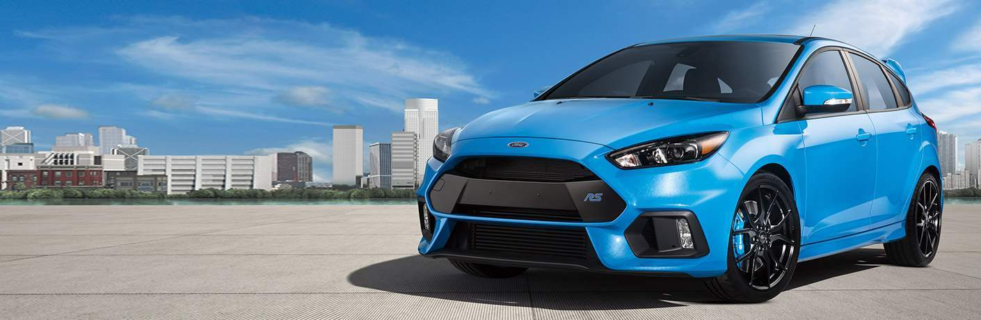 blue 2018 Ford Focus RS parked in an open area with a city skyline in the background