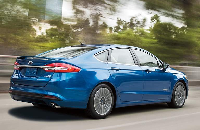 side view of a blue 2018 Ford Fusion driving down a tree lined road