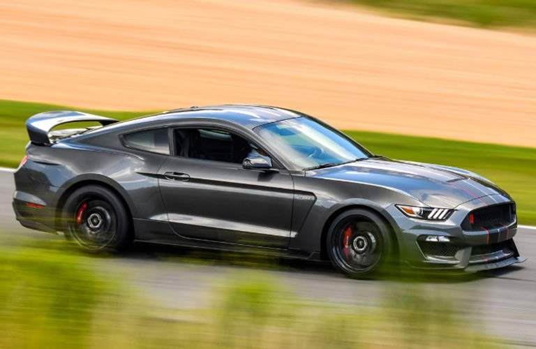 side view of a gray 2018 Ford Mustang GT cruising along a track