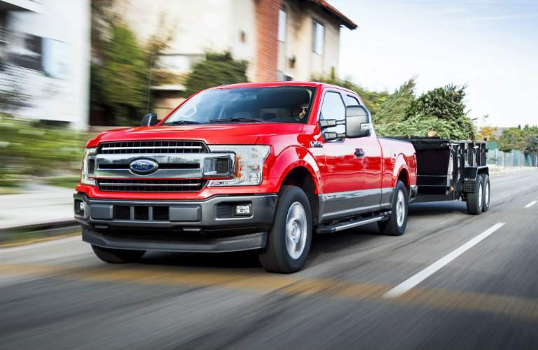 red 2018 Ford F-150 Diesel towing a trailer full of trees