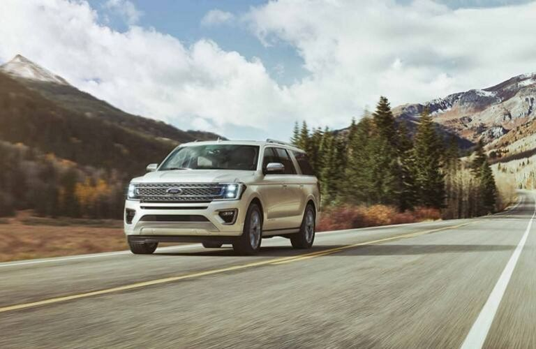 2019 Ford Expedition XLT driving down road near mountain terrain