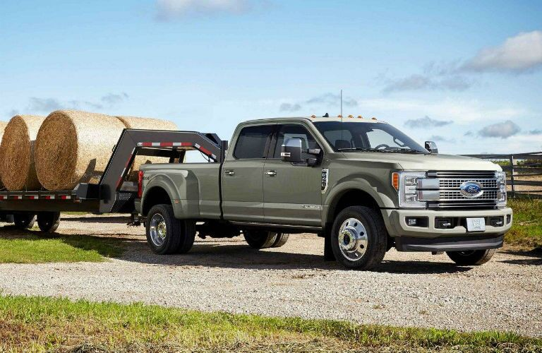 side view of a tan 2019 Ford F-450 Super Duty towing large hay bales