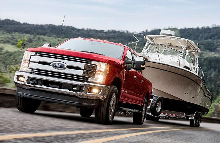 front view of a red 2019 Ford Super Duty towing a boat