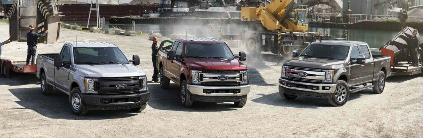 three 2019 Ford Super Duty trucks parked next to each other in a construction site