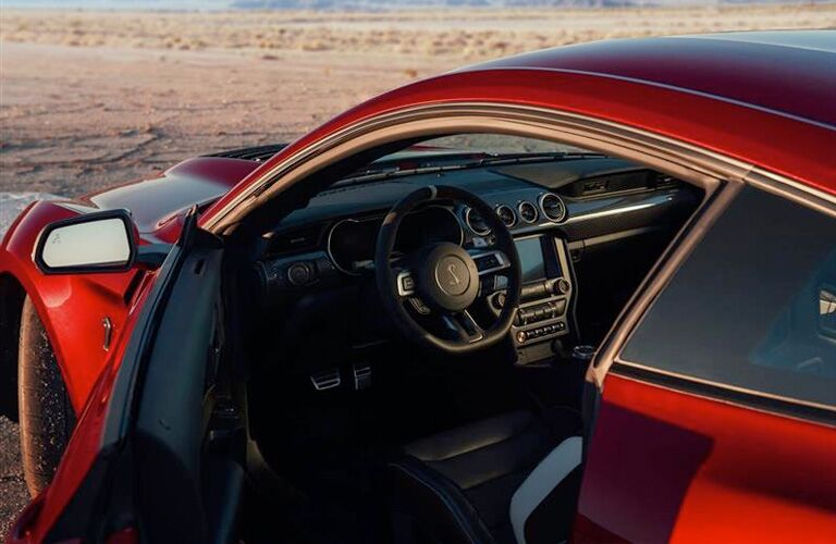side view of a red 2020 Ford Mustang Shelby GT500 with its driver door open