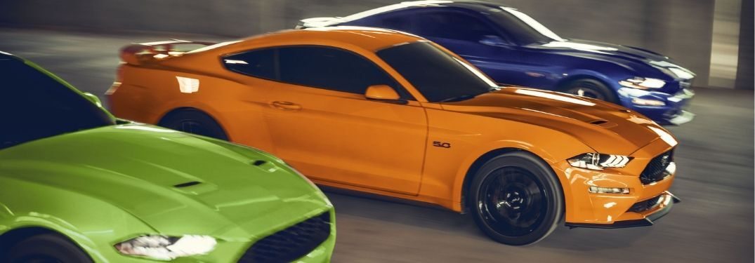 three 2020 Ford Mustang GTs racing down road