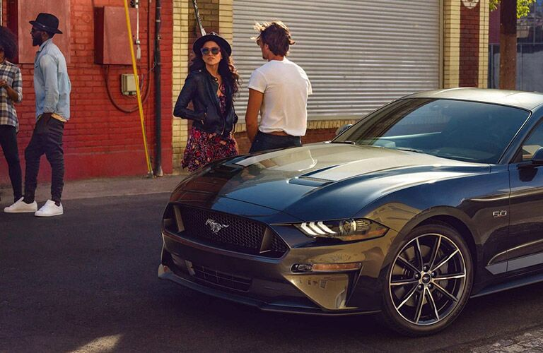 People standing near a parked 2021 Ford Mustang