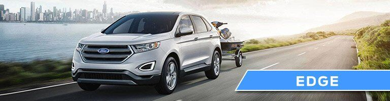 silver Ford Edge towing a jet ski along a coastal road