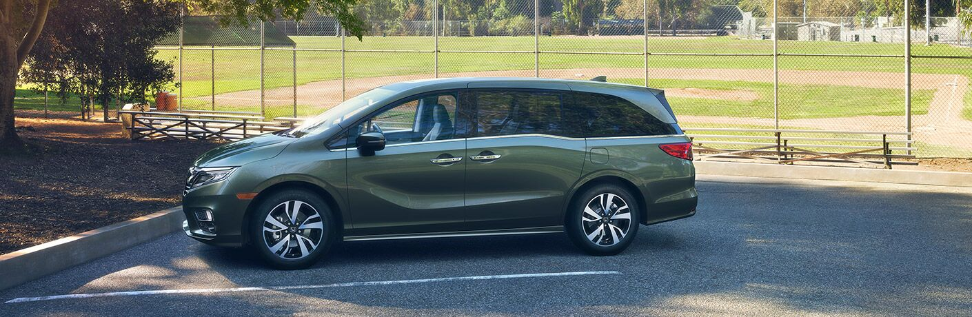 A left profile photo of the 2018 Honda Odyssey parked in front of a baseball field.