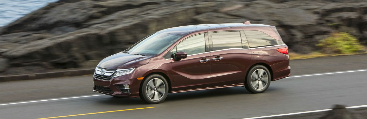 A left profile photo of the 2019 Honda Odyssey in motion on the road.