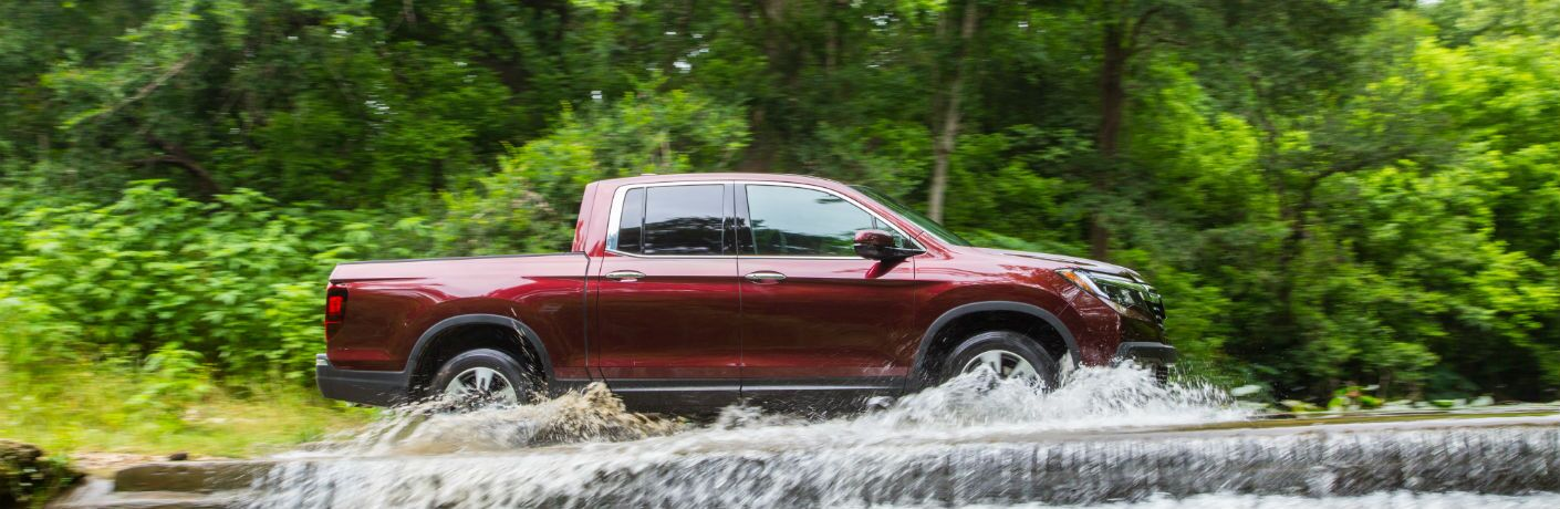 A right profile photo of the 2019 Honda Ridgeline crossing a shallow river.