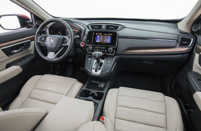 A photo showing the driver's cockpit including steering wheel, gauge cluster and infotainment system in the 2018 CR-V.