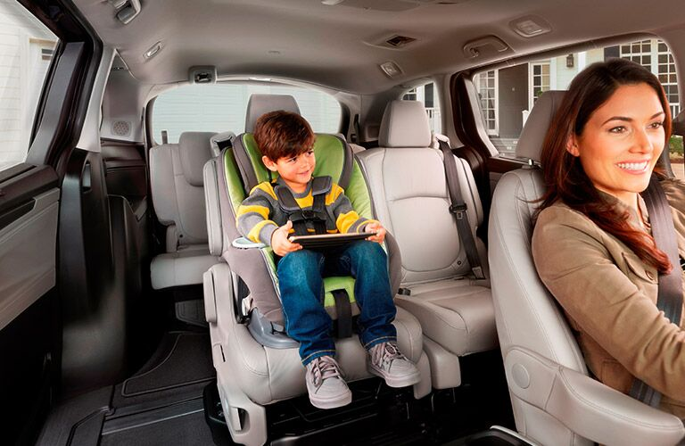 An interior showing a child in a car seat in the second row of the 2018 Odyssey.