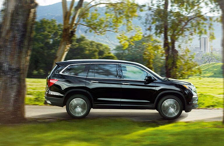 Honda Pilot Driving on Road through Trees Side Exterior View in Navy
