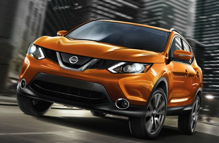 orange 2017 Nissan Rogue Sport exterior front driving down street