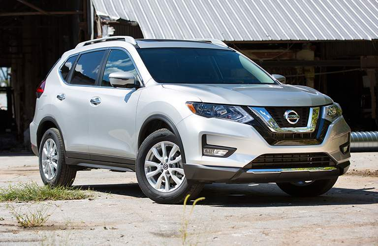 Silver 2018 Nissan Rogue parked in front of warehous