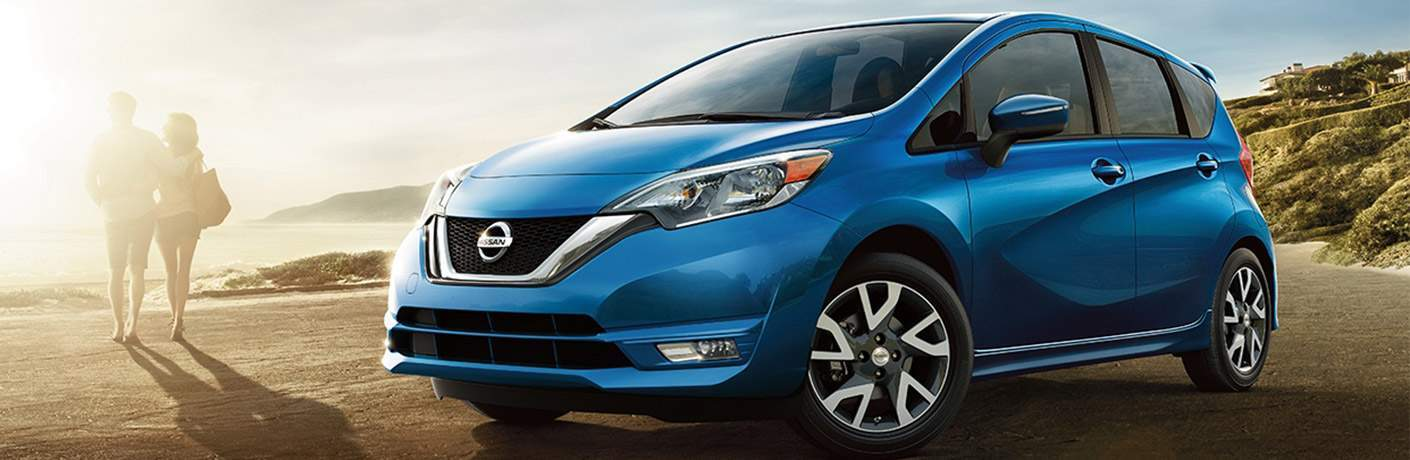 Blue 2018 Nissan Versa Note parked in front of couple walking toward beach