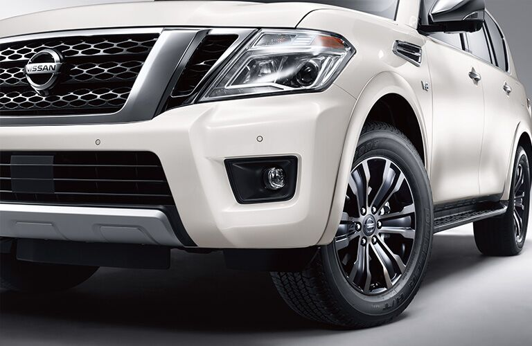 Close up of the driver headlight and wheel on a white 2019 Nissan Armada