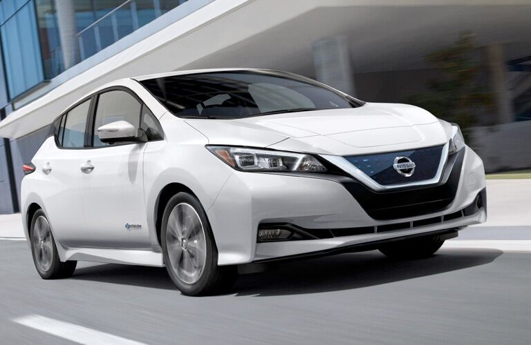 White 2019 Nissan LEAF drives down a city street in the day, looking sleek.