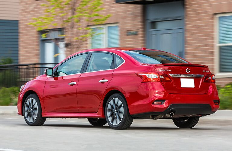 Rear driver angle of a red 2019 Nissan Sentra driving down a street