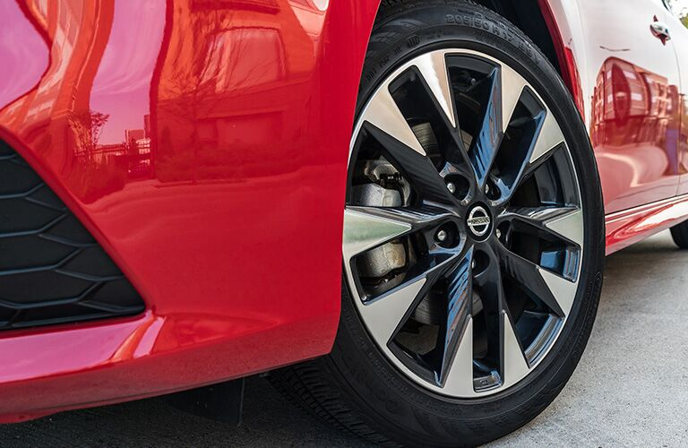 Up close view of the wheel on a red 2019 Nissan Sentra