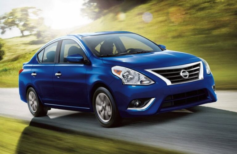 2019 Nissan Versa driving down a sunny rural road