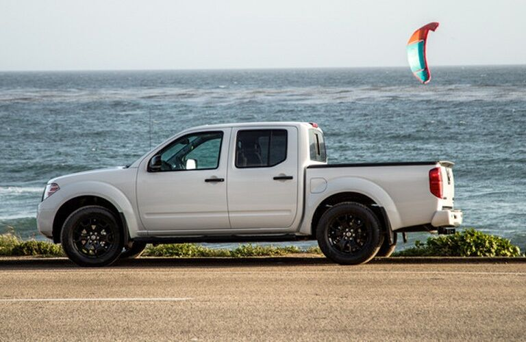 Side view of a white 2019 Nissan Frontier by ocean
