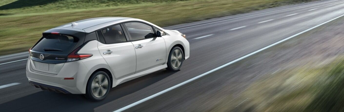 White 2019 Nissan LEAF driving on open road