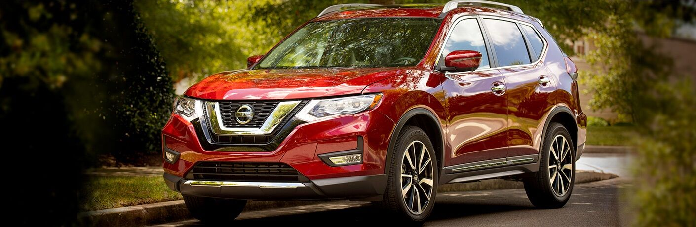 Red 2019 Nissan Rogue in a residential neighborhood