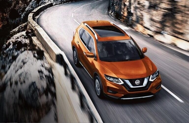 Orange 2019 Nissan Rogue driving on windy road