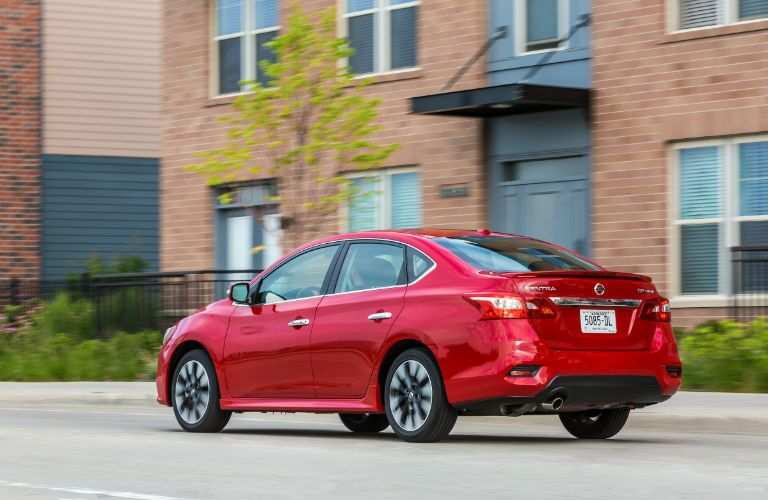 2019 Nissan Sentra driving past an apartment building