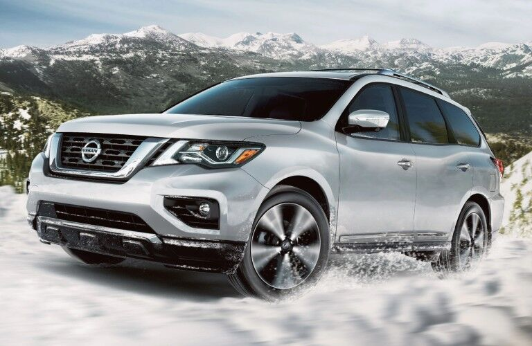 Front driver angle of a white 2020 Nissan Pathfinder driving in snow