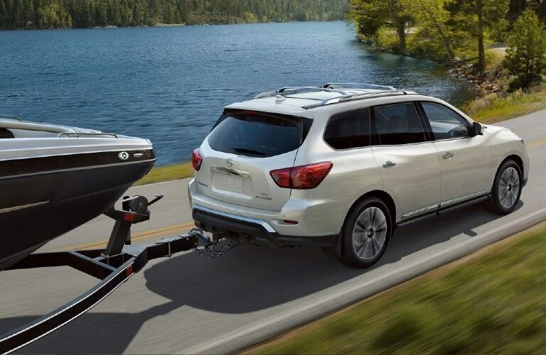 Rear passenger angle of a white 2020 Nissan Pathfinder towing a boat
