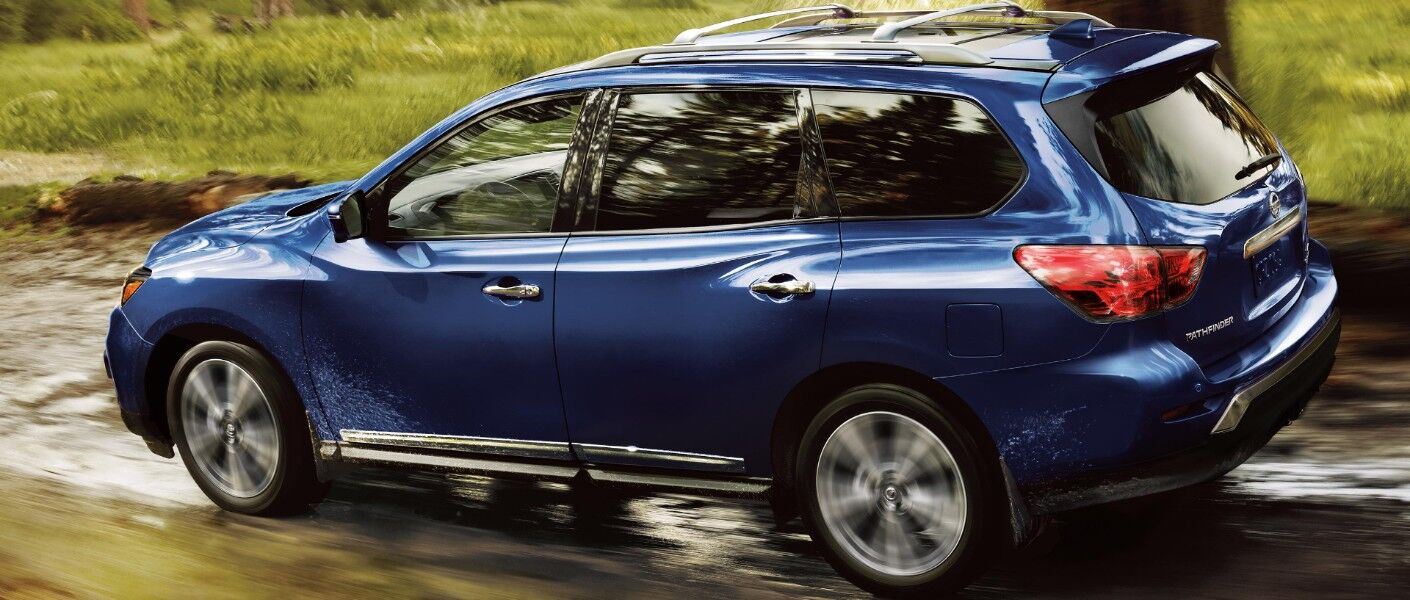 Profile view of blue 2020 Nissan Pathfinder driving on wet trail