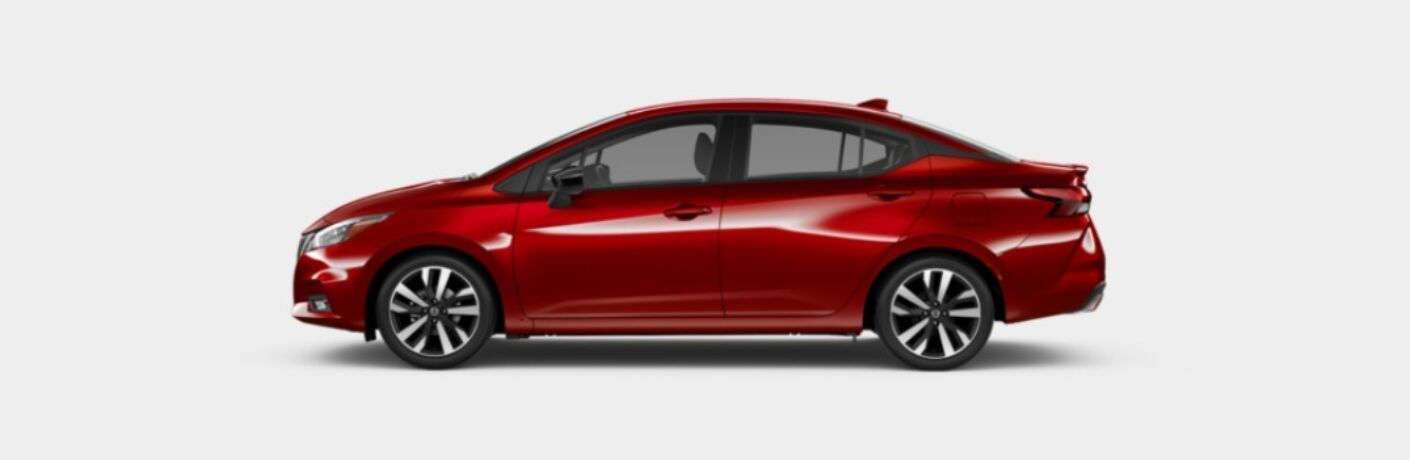 Side view of a red 2020 Nissan Versa SR on a gray background