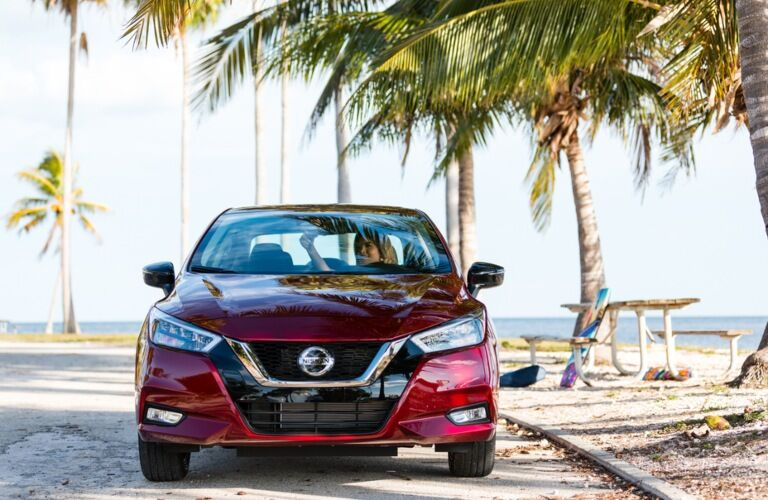 Front view of a red 2020 Nissan Versa on the beach