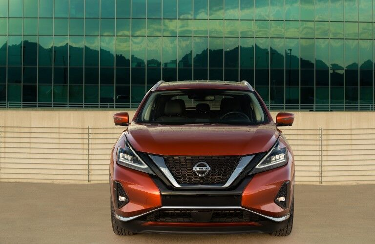 2021 Nissan Murano orange parked in front of glass facing shot