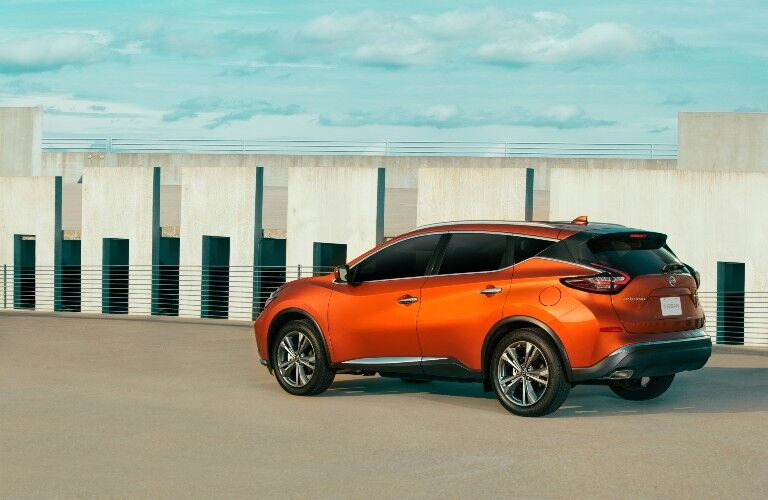 2021 Nissan Murano orange parked in open lot view of sky