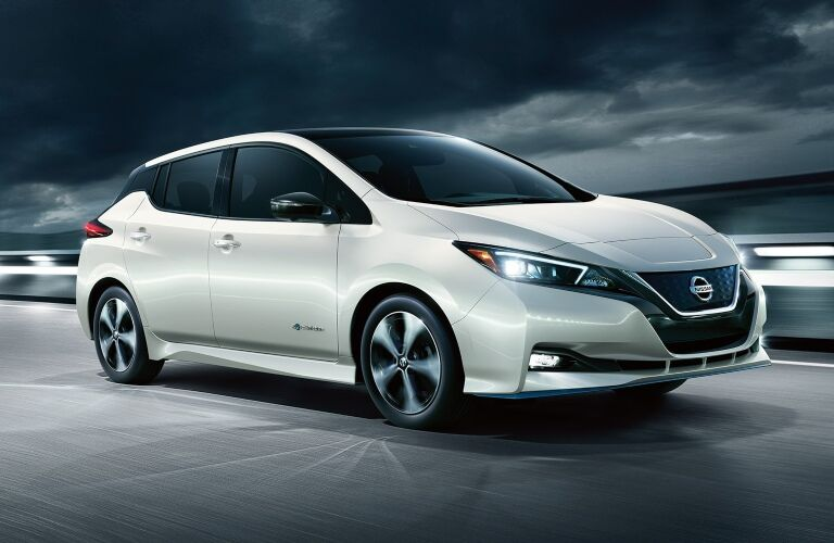 White 2019 Nissan LEAF driving in storm