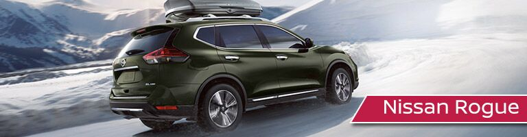 Green 2018 Nissan Rogue driving up snowy hill