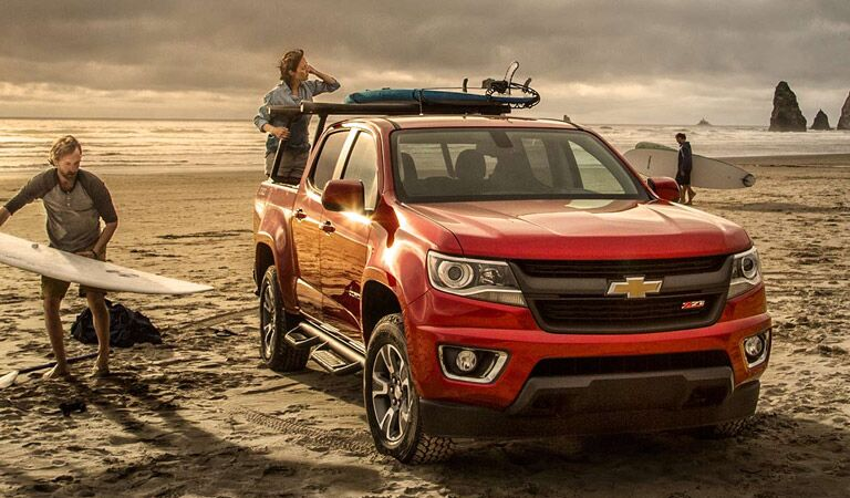Red Chevy Colorado midsize truck on the beach