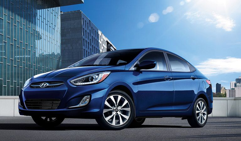 blue 2016 Hyundai Accent in front of skyscrapers