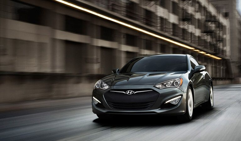 2016 Hyundai Genesis Coupe driving fast past high buildings