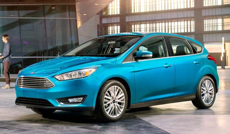 Turquoise Ford Focus sedan by a business