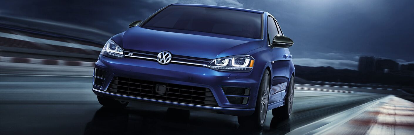 Exterior view of a blue 2018 Volkswagen Golf R driving around a wet race track at night