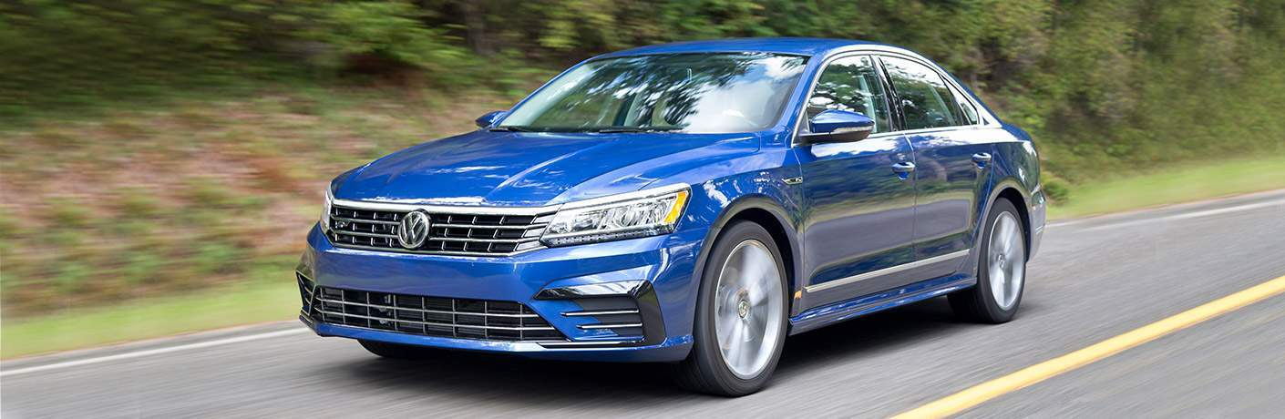 blue 2018 Volkswagen Passat front and side view, driving alongside trees