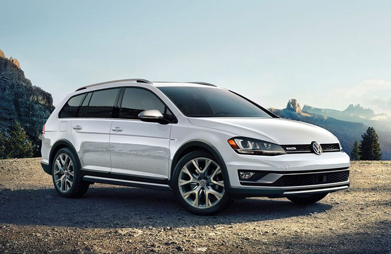 white Volkswagen Golf Alltrack parked by mountains and wide open spaces