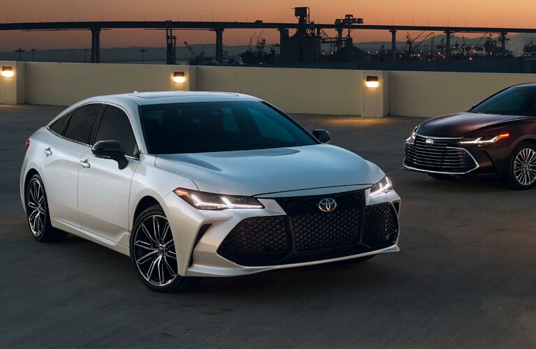 Two, 2019 Toyota Avalon Hybrid models parked on a roof at dusk