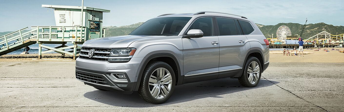 Silver-colored 2019 Volkswagen Atlas parked near an ocean-side carnival