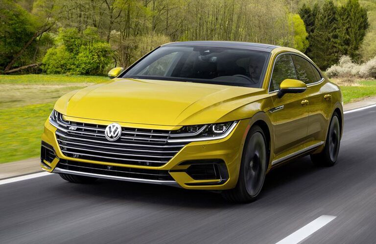 yellow Volkswagen Arteon driving by wooded area